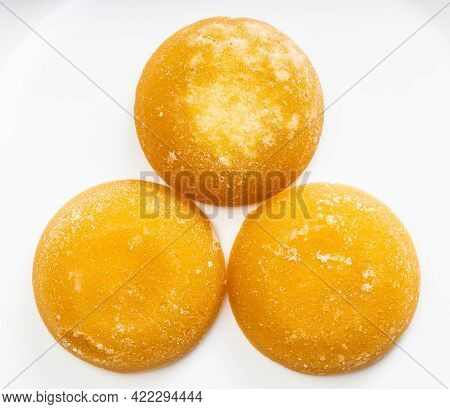 Top View Of Few Whole Round Pieces Of Palm Sugar On Gray Ceramic Plate