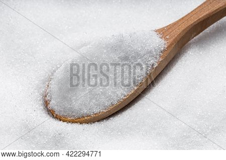 Above View Of Wooden Spoon With Crystalline Erythritol Sugar Substitute Close Up On Pile Of Sugar