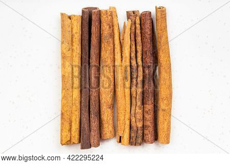 Top View Of Several Sticks Of Cassia Cinnamon Close Up On Gray Ceramic Plate