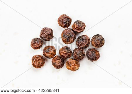 Several Red Kampot Peppercorns Close Up On Gray Ceramic Plate