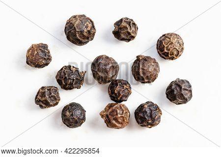 Several Black Pepper Peppercorns Close Up On Gray Ceramic Plate