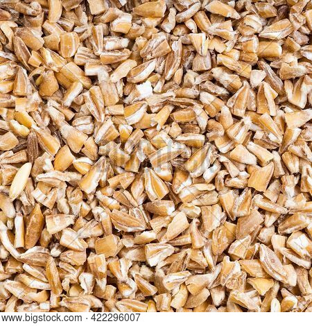 Square Food Background - Uncooked Crushed Emmer Farro Hulled Wheat Groats Close Up