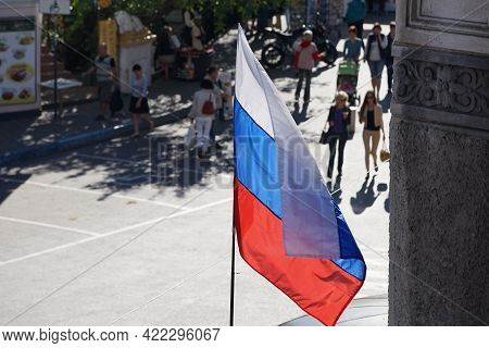 Russian Flag On A Blurry Street Background. Yalta, Crimea