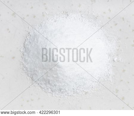 Top View Of Pile Of Crystalline Monosodium Glutamate Flavoring Close Up On Gray Ceramic Plate