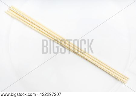 Several Dried Round Udon Noodles From Wheat Flour On White Plate