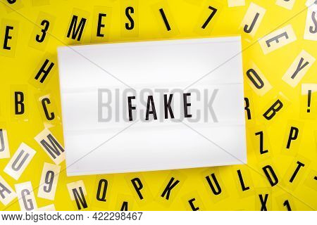 Lightbox With Text Message Fake On Yellow Background With Black Letters Randomly Scattered. Concept