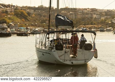 Sevastopol. Crimea. Winter 2021. Yacht In The Bay Of Sevastopol. Yacht In The Setting Sun From The S