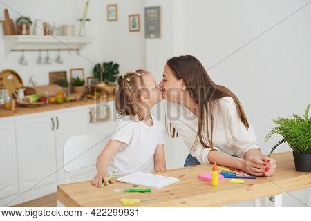 Mom And Daughter Have Finished Doing Their Homework, Are Happy And Kiss. The Concept Of Taking Care