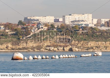 A Row Of Large Iron Barrels For Mooring Ships. Buoys On The Background Of The City Of Sevastopol Ins