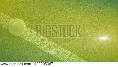 Composition of tennis ball on white line on tennis court with light and green tinted background. sports and competition concept digitally generated image.