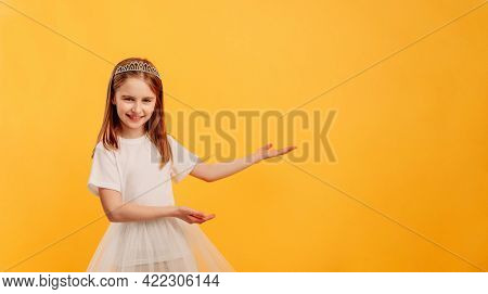 Little girl wearing princess dress and diadem posing isolated on yellow background with copyspace. Pretty female kid looing at the camera and smiling