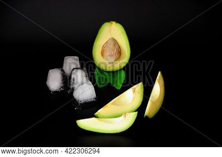 Sliced Ripe Avocado Slices With Melted Ice Cubes On A Black Background.