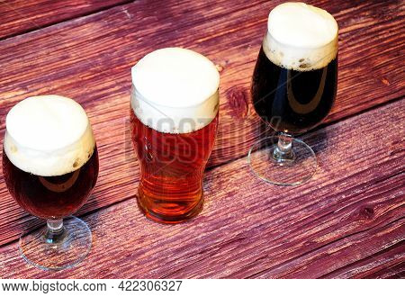 Three Glass Goblets With Different Types Of Dark Beer Stand On A Wooden Table.