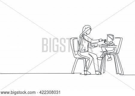One Single Line Drawing Of Young Mother Feeding Her Son A Meal Who Sit At Baby Dining Chair At Home