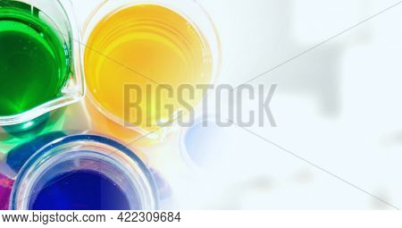 Composition of overhead view of colourful liquids in beakers, with white copy space to right. medical and science research concept digitally generated image.