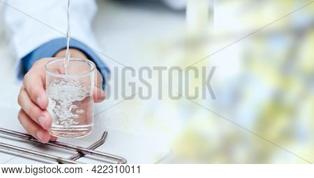 Composition of hand holding liquid in chemistry beaker, with blurred copy space to right. medical and science research concept digitally generated image.