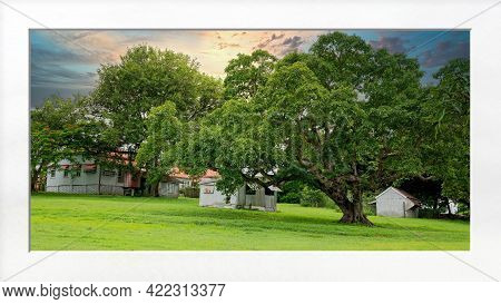 Sunset Over An Historic Homestead Set In Parkland Amongst Lush Green Grass With White Mat Framing