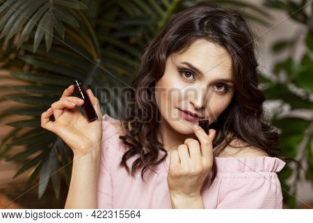Young Woman With Aroma Oil In Her Hand. Enjoy The Scent Of Nature. Beautiful Brunette In A Pink Swea