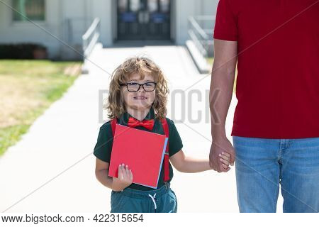 Father Supports And Motivates Son, Holding Hand Outdoors, Back To School. Kid Nerd Going To Primary