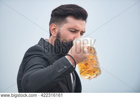 Hipster With Beard And Mustache In Suit Drinks Beer After Working Day. Germany Bavaria. Beer Time. H