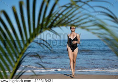 Happy Smiling Woman Run On The Beach. Beautiful Young Woman Running On Tropical Beach. Tropical Summ