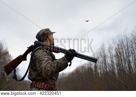 A Hunter With An Unloaded Shotgun On His Shoulder Stands In The Twilight In A Forest Clearing. He Lo