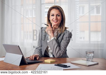 Business woman face Portrait. Business woman portrait working on computer in office. Business woman working in office. Beautiful business woman. Woman portrait in office. Woman in office business working on computer. Business woman portrait working on lap