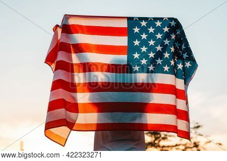 Independence Day. Silhouette Of Woman Holds An American Flag In Her Hands, Raised Above Her Head. Ba