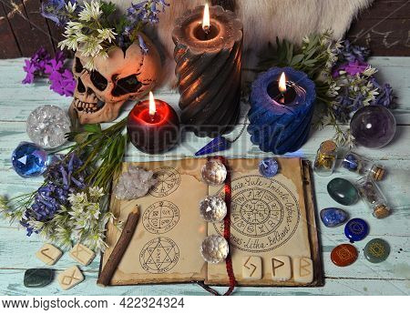 Still Life With Open Witch Book, Crystal, Burning Candles And Flowers On Altar Table. Esoteric, Goth
