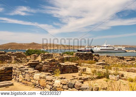 View Of A Bay On Delos Island, Greece, With Tourist Ships From Mykonos Anchored And Ancient Town Rui