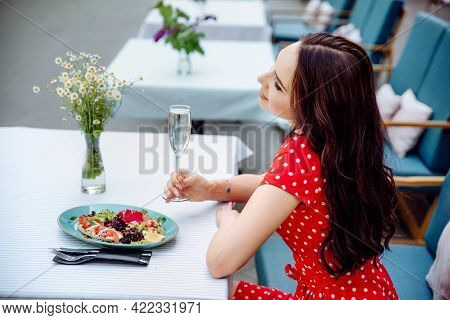 Ecstatic Brunette Girl Chilling In Cafe. Inspired Young Woman In Red Polka Dot Dress Enjoying Champa