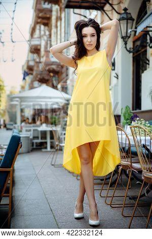Portrait Of A Girl Posing In City Near Summer Terrace. Dressed In Yellow Dress. Fashion Portrait Sty