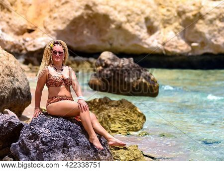 A Slender Girl With Curly Hair In A Swimsuit Sits On A Stone On The Shores Of The Red Sea In Egypt.