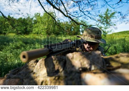 Airsoft Player In Camouflage Uniform Aiming At The Sight Of A Weapon From Behind Cover