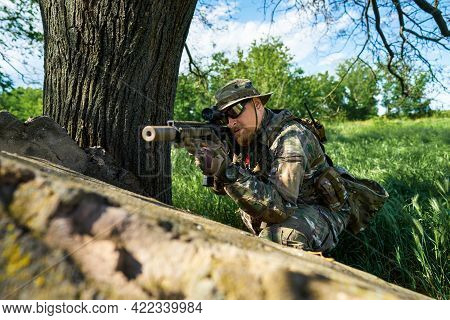A Soldier In Camouflage Uniforms Aiming At The Sight Of A Weapon
