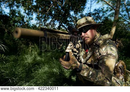 Airsoft Player In Camouflage Uniform Aiming At The Sight Of The Weapon