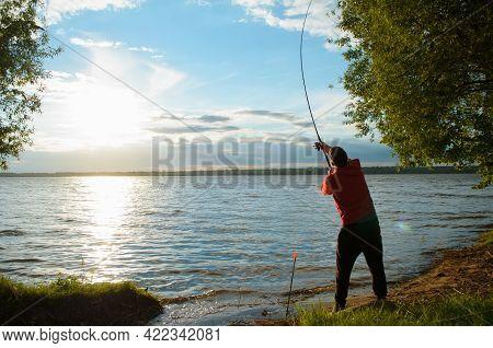 Fisherman On The Lake. Man Throws Spinning Rod, Back View . Fishing At Sunset. Setting Sun, Lake Sho