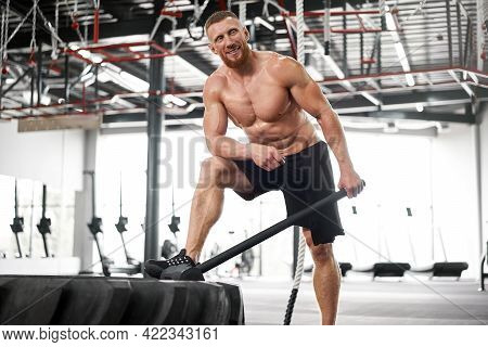 Man Gym Hammer Hit Tractor Wheel Hitting Huge Tire Athlete Sportive Man Middle Adult Handsome Sports