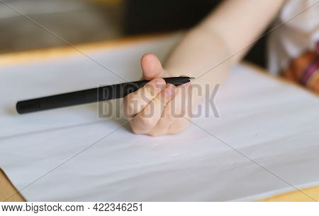 A Child's Hand Holds A Large Black Ballpoint Pen And Draws On A White Piece Of Paper. A Little Three