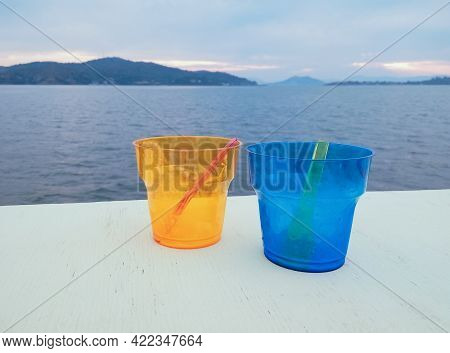 Two Colourful Plastic Cups Empty After Dessert, With Spoons Inside, On A White Table, Beach And Moun