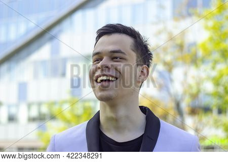Street Portrait Of A Laughing Young Man 18-20 Years Old In A White Jacket On The Background Of An Of