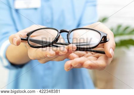 Woman Doctor Optometrist In Blue Uniform Holds In Her Hands And Gives A Pair Of Glasses To A Patient