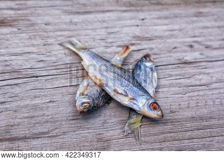 Sun Dried Salted Fish - Sea Roach On Old Wooden Table Surface.