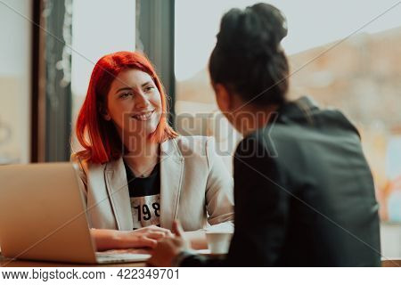 Two young business women sitting at table in cafe. Girl shows colleague information on laptop screen. Girl using smartphone, blogging. Teamwork, business meeting.