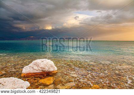 The sun illuminates the Jordanian coast. Israeli coast. Rocky beach covered with evaporated salt. The Dead Sea, sunset. Gloomy sky with dark thunderclouds.