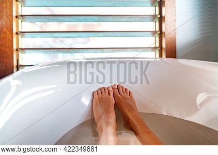 Bathtub feet soaking in warm water woman taking a warm bath at luxury bathroom villa. Window view.