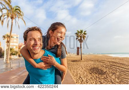 Happy interracial couple laughing in love Asian woman piggyback on smiling caucasian man lovers. Perfect dental smile models portrait in summer beach travel city lifestyle.