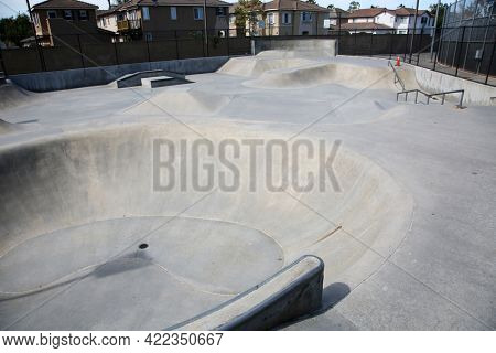 May 27, 2021 Irvine California: View of outdoor concrete skate park with ramps and pipes in California. Skate Parks are a great place for kids to do tricks and practice skate boarding. Editorial.