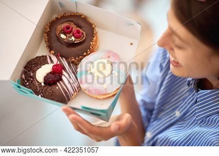 A beautiful girl in a pleasant atmosphere in a pastry shop is passionately looking at a box with delicious donuts she holds in her hands. Pastry shop, dessert, sweet