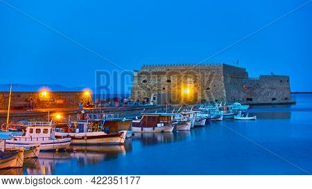 Heraklion in Crete Island, Greece.  Harbor with fishing boats by the old venetian fortress at dusk